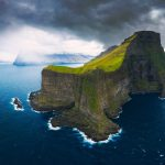 Widok z lotu ptaka małej białej latarni morskiej położonej na skraju ogromnego klifu i wyspy Kalsoy. Kalsoy to odizolowana mała wyspa w północno-wschodniej części Wysp Owczych.